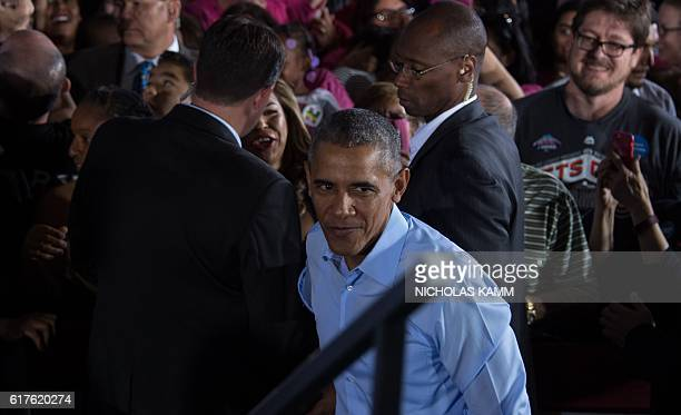 US President Barack Obama walks back onto the stage after shaking hands following his speech at a campaign event for Democratic presidential...