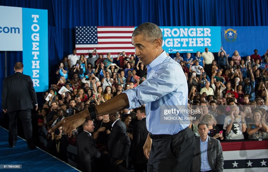 President Barack Obama walks back onto the stage after shaking hands following his speech at a campaign event for Democratic presidential candidate Hillary Clinton in Las Vegas on October 23, 2016. / AFP / NICHOLAS