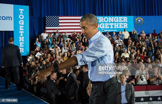 President Barack Obama walks back onto the stage after shaking hands following his speech at a campaign event for Democratic presidential candidate...