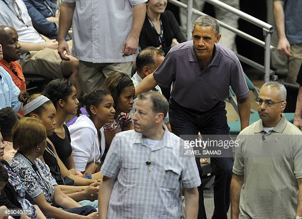 US President Barack Obama walks back to his seat during the Oregon State University vs University of Akron college basketball game at the Diamond...