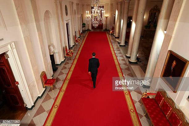 President Barack Obama walks down the Cross Hall at the end of a news conference in the East Room of the White House in Washington DC