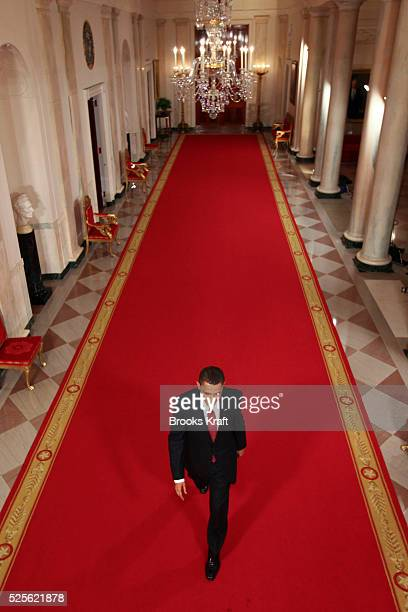 President Barack Obama walks down the Cross Hall towards a news conference in the East Room of the White House in Washington DC