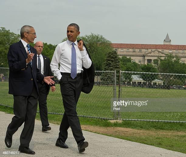 S President Barack Obama walks from the White House to the United States Department of the Interior accompanied by White House advisor John Podesta...