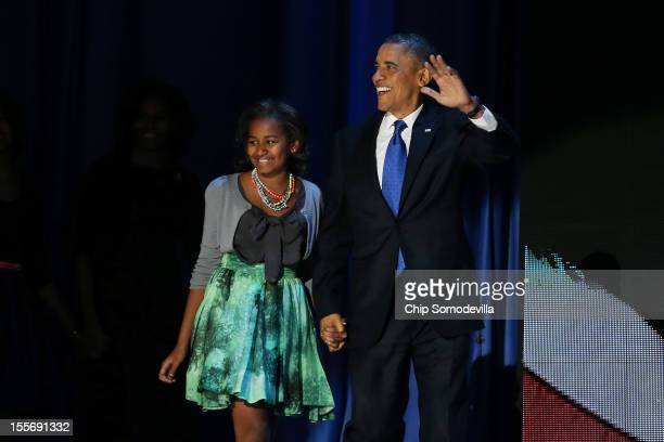 S President Barack Obama walks on stage with daughter Sasha to deliver his victory speech on election night at McCormick Place November 6 2012 in...