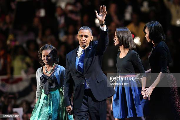 President Barack Obama walks on stage with first lady Michelle Obama and daughters Sasha and Malia to deliver his victory speech on election night at...
