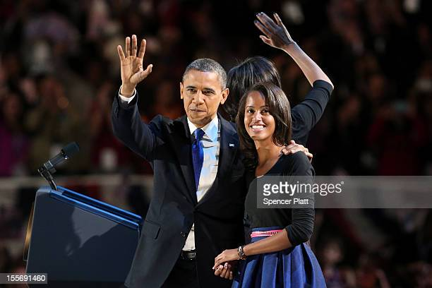 S President Barack Obama walks on stage with first lady Michelle Obama and daughters Sasha and Malia to deliver his victory speech on election night...