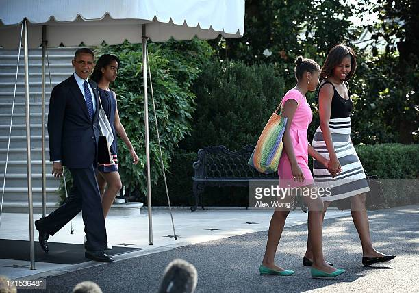 S President Barack Obama walks out from the residence with first lady Michelle Obama daughters Sasha and Malia prior the their departure for a trip...
