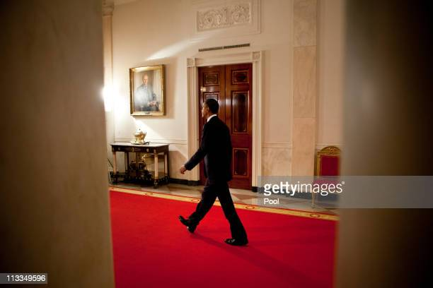 US President Barack Obama walks through the Cross Hall of the White House to make a televised statement May 1 2011 in Washington DC Bin Laden has...