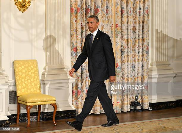 US President Barack Obama walks to the podium to address the nation in the State Dining Room of the White House on August 7 2014 in Washington DC...