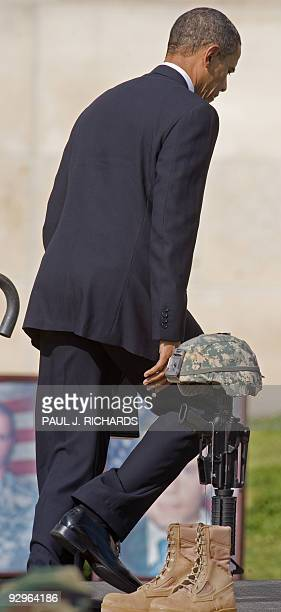 US President Barack Obama walks to the stage past one of the 13 pairs of boots a rifle and a helmet memorials during the Fallen Soldier Memorial at...