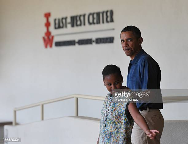 US President Barack Obama walks with his daughter Sasha after a visit to the EastWest Center at the University of Hawaii January 1 2012 in Honolulu...