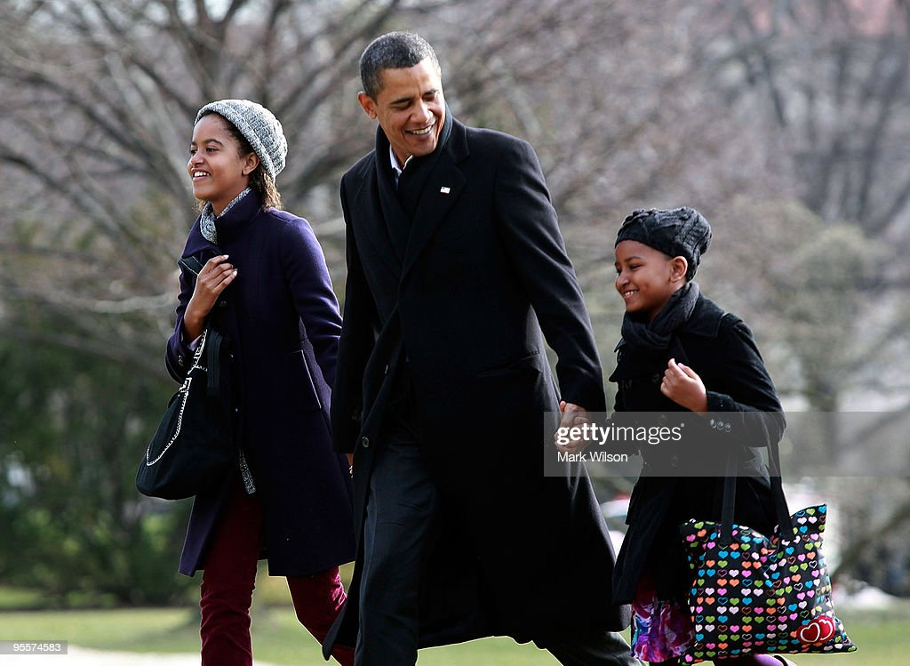 US President Barack Obama (C) walks with his daughters Malia (L) and Sasha (R) after they arrive on the South Lawn of the White House on January 4, 2010 in Washington, DC. President Obama and his family were returning from Hawaii where they spent Christmas vacation.