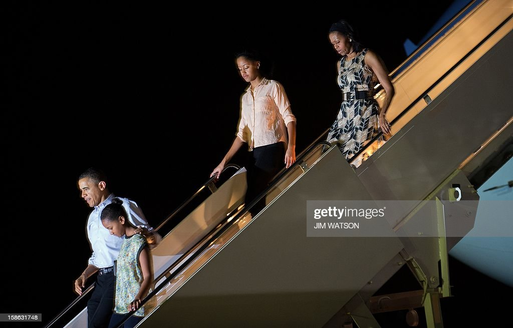 US President Barack Obama (L) walks with his daughters Sasha (2nd L) and Malia (2nd R), as well as First Lady Michelle Obama (R), off Air Force One at Hickham Feild in Honolulu, Hawaii, early on December 22, 2012. Obama told lawmakers December 21, 2012, to go home and drink some Christmas egg nog before coming back to Washington to pass a scaled-down tax package to avert a year-end fiscal crisis. Obama said he still wanted a comprehensive and large deficit-cutting bill to put the US economy on the path to long-term prosperity, but that effort stalled when talks broke down between the White House and House Republicans this week. AFP PHOTO / Jim WATSON