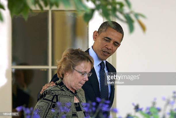 S President Barack Obama walks with Janice Baker a business owner in Delaware who was the first person in her state to enroll in insurance through...