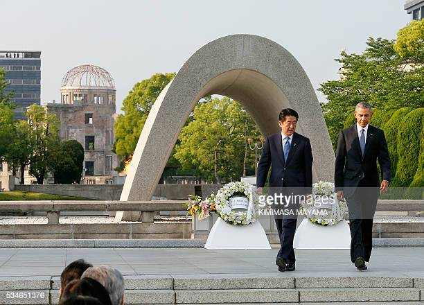 US President Barack Obama walks with Japanese Prime Minister Shinzo Abe after laying wreaths in front of a cenotaph to offer a prayer for victims of...