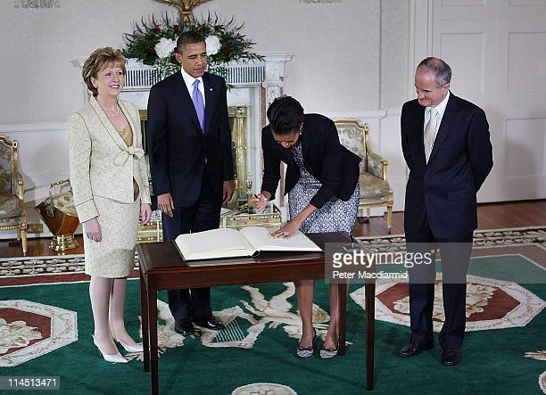 President Barack Obama watches as First Lady Michelle Obama signs a visitors book as President of Ireland Mary McAleese and Dr. Martin McAleese look...