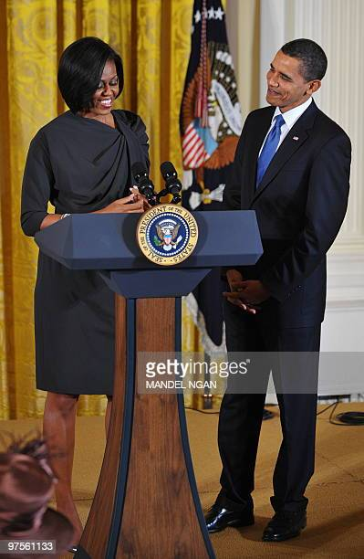 US President Barack Obama watches as First Lady Michelle Obama speaks during a reception marking International Women�s Day March 8 2010 in the East...