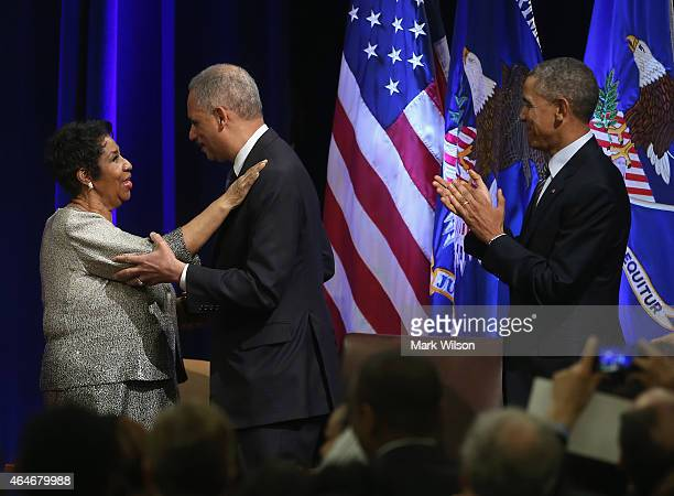 President Barack Obama watches as US Attorney General Eric Holder gets a hug from singer Aretha Franklin after she sang America The Beautiful during...