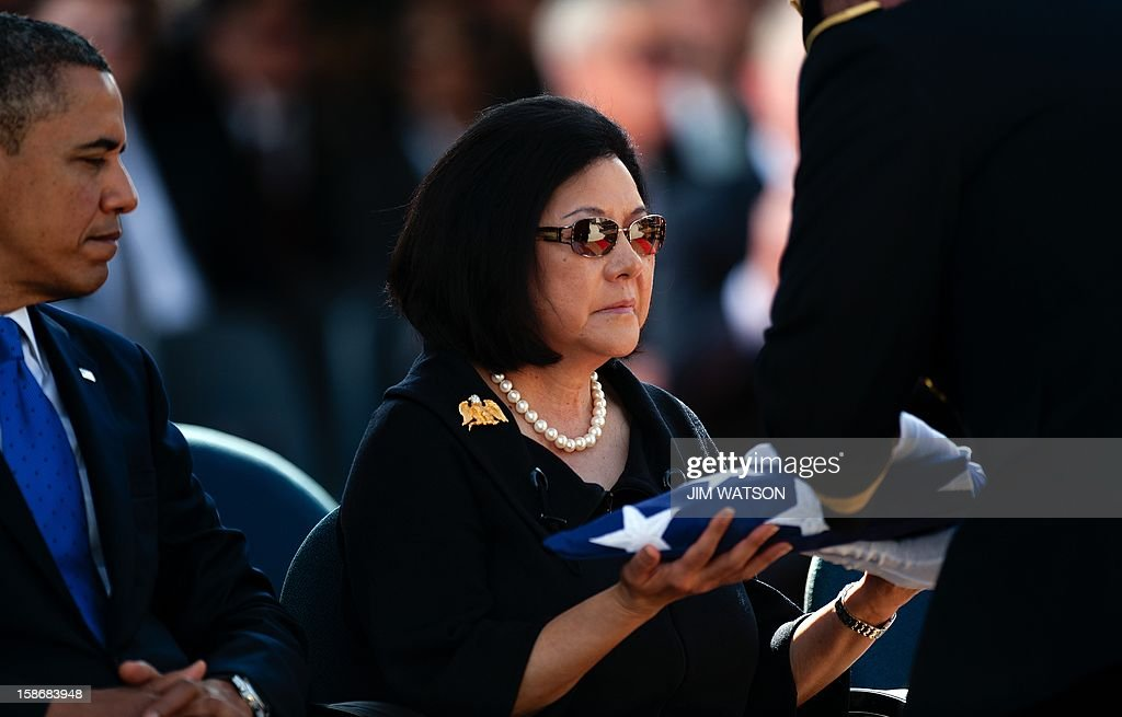 US President Barack Obama (L) watches as widow Irene Hirano Inouye (C) recieves a folded flag that draped her husbands coffin during the memorial service for the late Senator Daniel Inouye at the National Memorial Cremetary of the Pacific in Honolulu, Hawaii, December 23, 2012. AFP Photo/Jim WATSON