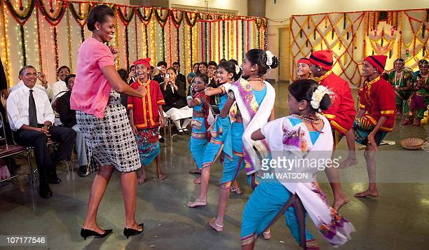 US President Barack Obama watches First Lady Michelle Obama dance during a cultural event at The Holy Name High School in Mumbai on November 7 2010...