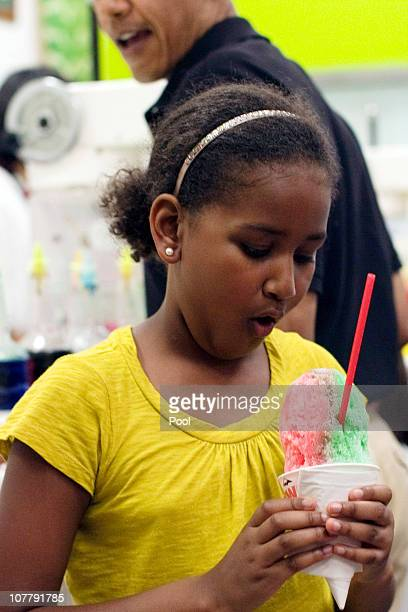 US President Barack Obama watches his daughter Sasha Obama admire her shave ice at Island Snow at Kailua Beach Center in Kailua Hawaii December 27...