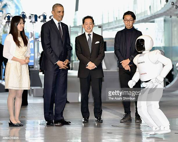 US President Barack Obama watches Honda Motor Co humanoid robot ASIMO hops with the Miraikan chief executive dierector Mamoru Mohri on April 24 2014...