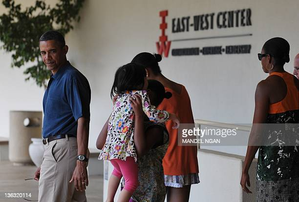 US President Barack Obama watches while his daughter Sasha picks up his niece Savita Ng after a visit to the EastWest Center at the University of...