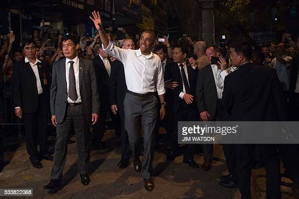 US President Barack Obama waves after eating dinner at Bun cha Huong Lien with CNN's Anthony Bourdain in Hanoi late on May 23 2016 Obama praised...