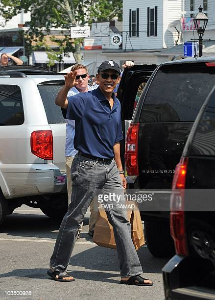 US President Barack Obama waves after shopping at Bunch of Grapes bookstore with his daughters Malia and Sasha in Vineyard Haven on Martha's Vineyard...