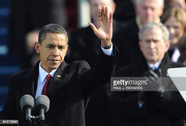US President Barack Obama waves as former president George W Bush applauds after Obama's inaugural speech at the Capitol in Washington on January 20...