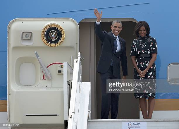 US President Barack Obama waves as he and First Lady Michelle Obama board Air Force One prior to departing from Air Force Station Palam in New Delhi...