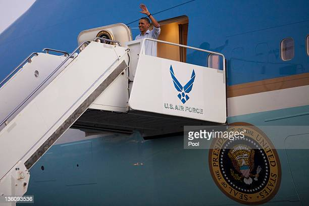 US President Barack Obama waves as he disembarks from Air Force One at Joint Base Pearl HarborHickam December 23 2011 in Honolulu Hawaii President...