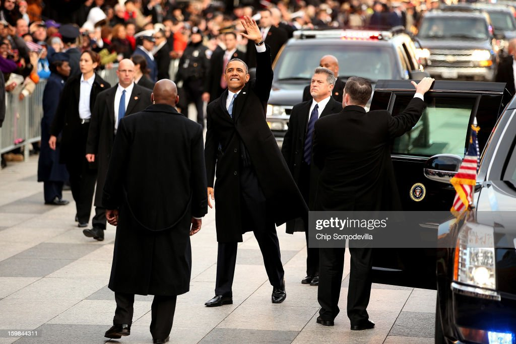 U.S. President Barack Obama waves as he exits the presidential limo as the inaugural parade winds through the nation's capital January 21, 2013 in Washington, DC. Barack Obama was re-elected for a second term as President of the United States.