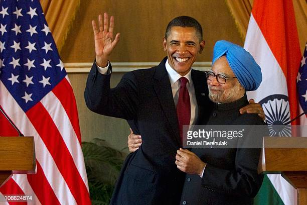 President Barack Obama waves as he is embraced by Indian Prime Minister Manmohan Singh after speaking during a joint press conference at Hyderabad...