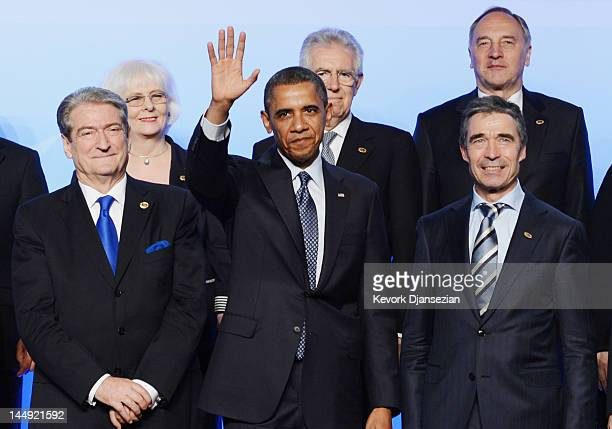 S President Barack Obama waves as he poses for the family photo with Prime Minister of Albania Sali Berisha and NATO Secretary General Anders Fogh...