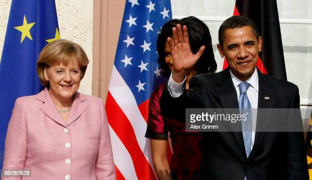 S President Barack Obama waves as he stands next to German Chancellor Angela Merkel and his wife Michelle upon his arrival for bilateral talks on...