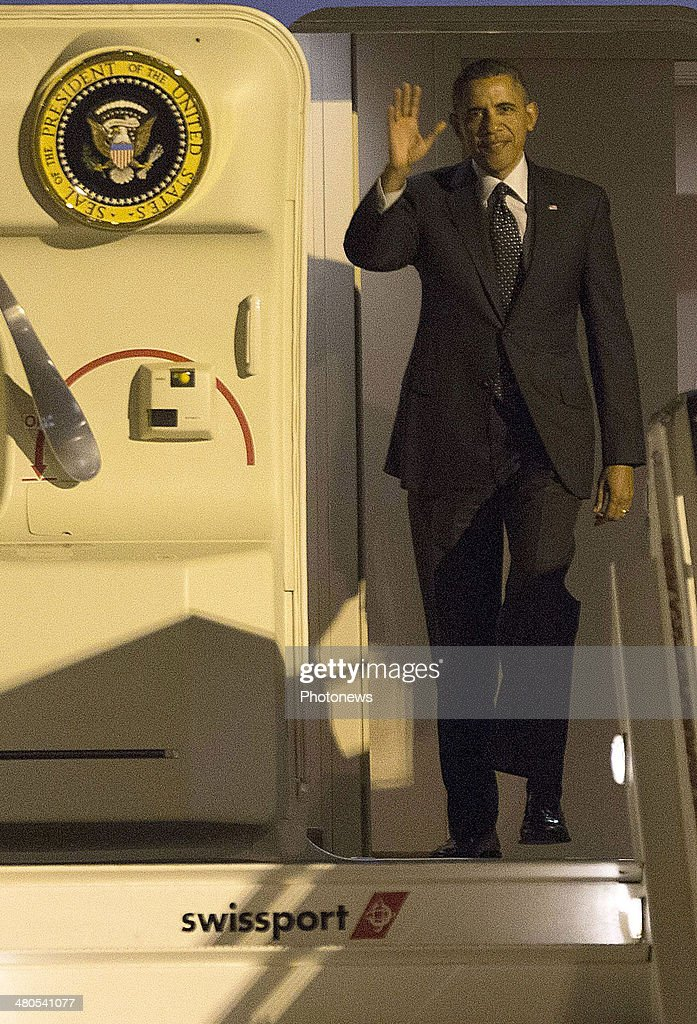US President Barack Obama waves as he walks down the stairs from Air Force One upon arrival at Zaventem Airport on March 25, 2014 in Brussels, Belgium.