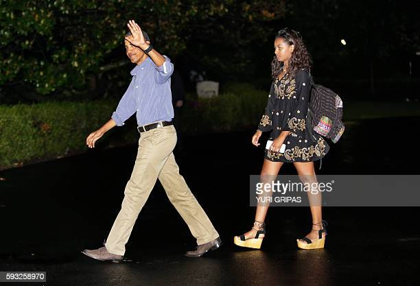 US President Barack Obama waves as he walks with daughter Sasha on the South Lawn of the White House in Washington upon their return from a summer...