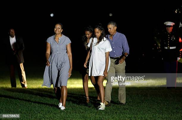 US President Barack Obama waves as he walks with First lady Michelle Obama and their daughters Malia and Sasha on the South Lawn of the White House...
