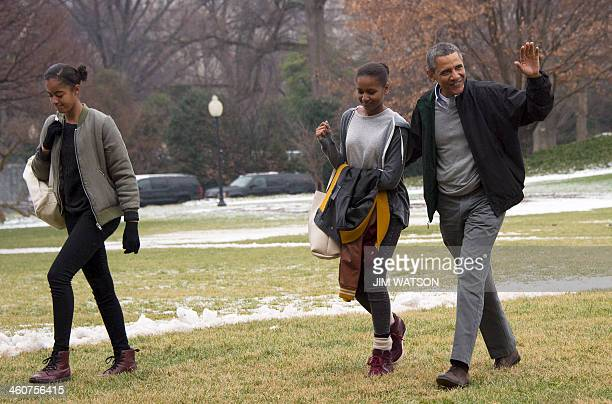 US President Barack Obama waves as he walks with his daughters Sasha and Malia as they arrive back at the White House in Washington DC January 5 2014...