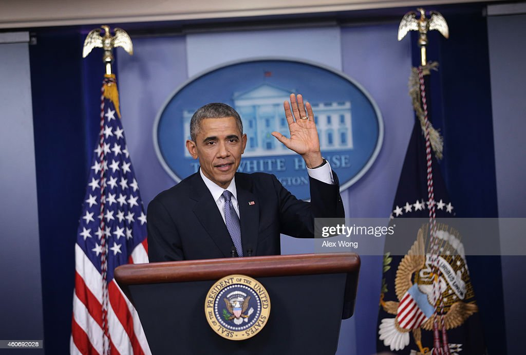 U.S. President Barack Obama waves at the end of his last news conference of the year in the James Brady Press Briefing Room of the White House December 19, 2014 in Washington, DC. President Obama faced questions on various topics including the changing of Cuba policy, his executive action on immigration and the Sony hack.