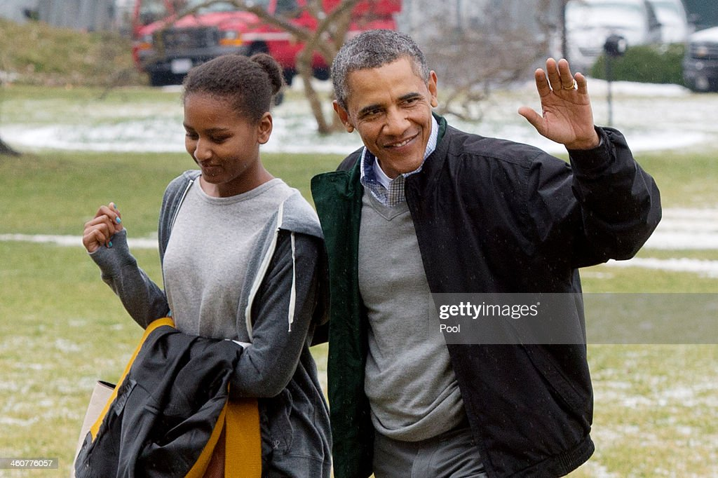 U.S. President Barack Obama (R) waves beside his daughter Sasha (L) as they walk across the South Lawn of the White House after arriving by Marine One January 5, 2014 in Washington, DC. Obama returns from a two-week holiday in Hawaii.