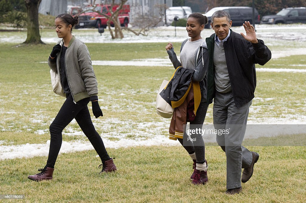 U.S. President Barack Obama (R) waves beside his daughters Malia (L) and Sasha (C), as they walk across the South Lawn of the White House after arriving by Marine One January 5, 2014 in Washington, DC. Obama returns from a two-week holiday in Hawaii.