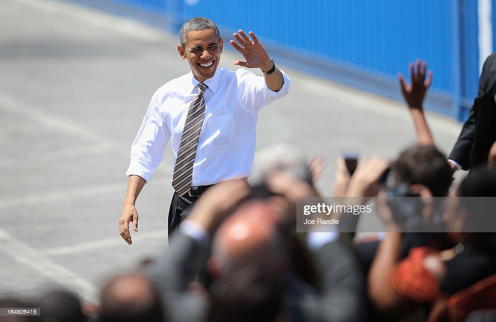 President Barack Obama waves during an event at PortMiami on March 29, 2013 in Miami, Florida. The president spoke about road and bridge construction during the event at the port in Miami, where he also toured a new tunnel project.
