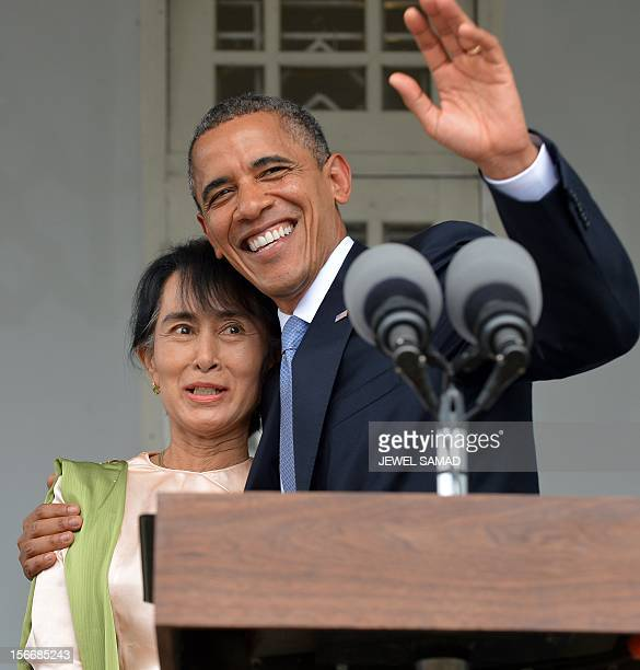 US President Barack Obama waves holding Myanmar opposition leader Aung San Suu Kyi after making a speech at her residence in Yangon on November 19...