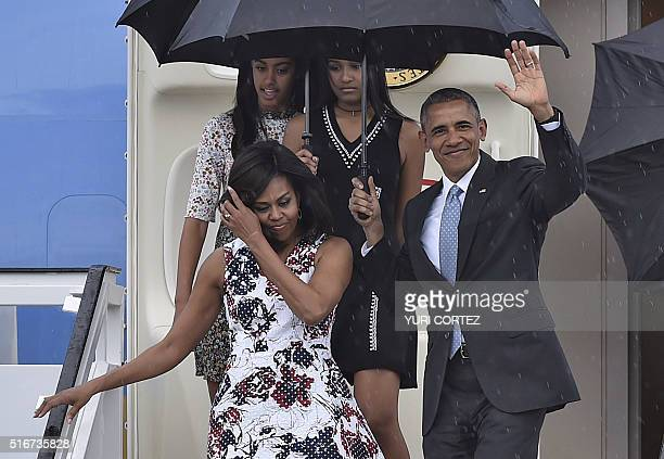 President Barack Obama waves next to First Lady Michelle Obama and their daughters Malia and Sasha upon their arrival at Jose Marti international...