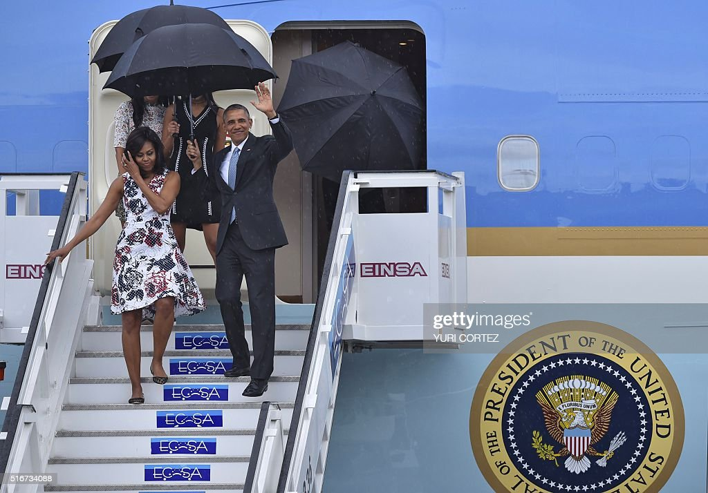US President Barack Obama waves next to First Lady Michelle Obama as they arrive with their daughters Sasha and Malia (behind) at Jose Marti international airport in Havana on March 20, 2016. Obama, who is on a historic three-day visit to the communist-ruled island, flew to Cuba Sunday to bury the hatchet in a more than half-century-long Cold War standoff, but the arrest of dozens of dissidents just as his plane took off underlined the delicacy of the mission. AFP PHOTO/ Yuri CORTEZ / AFP / YURI