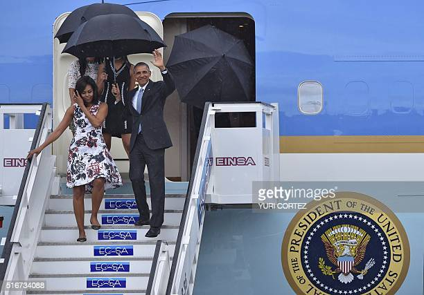US President Barack Obama waves next to First Lady Michelle Obama as they arrive with their daughters Sasha and Malia at Jose Marti international...