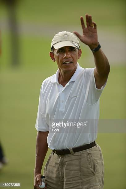 S President Barack Obama waves to a small crowd waiting along a road near the 18th hole at the Mid Pacific Country Club on January 1 2014 in Lanikai...