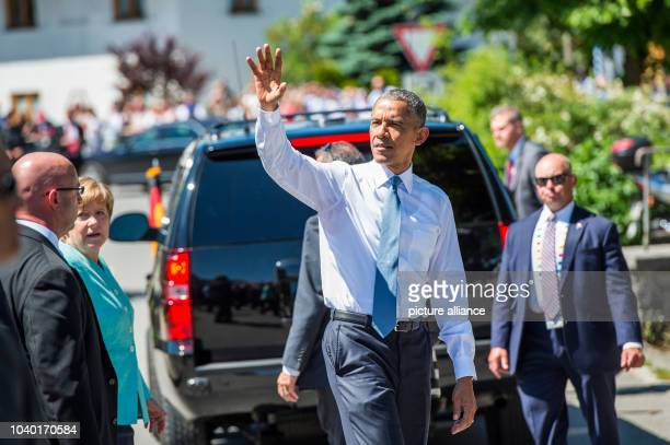 President Barack Obama waves to members of the public in Kruen, Germany, 07 June 2015 as he joins with German Chancellor Angela Merkel before they...